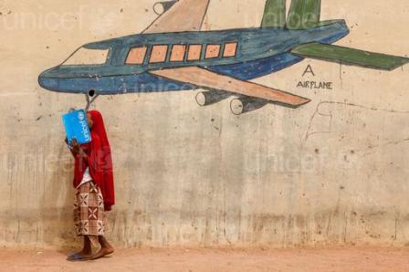 Le 17 Mars, Alia, 10, couvre son visage avec un dossier tout en se tenant devant une fresque murale d'un avion, dans un camp pour personnes déplacées à l'intérieur, à Yola, capitale de l'Adamaoua, un état dans le nord-est du Nigéria.